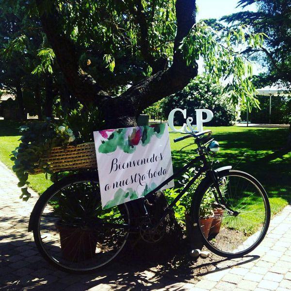 Bicicleta en un jardín con cartel de bienvenida