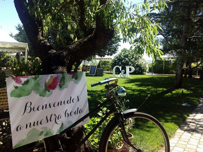 Cartel de bienvenida en un jardín sobre bicicleta