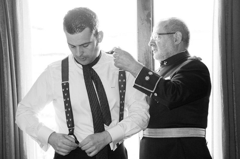 Padre vistiendo a su hijo para la boda